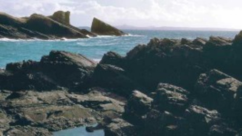 View from the beach at Clachtoll, showing the sea and rocks protruding from the water.